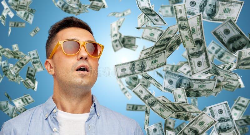 Удивленный человек под дождем денег доллара стоковые фотографии rf