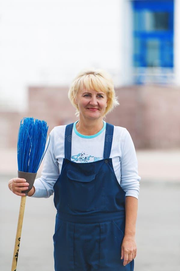 Улица города чистки портрета работника с инструментом веника стоковое фото rf