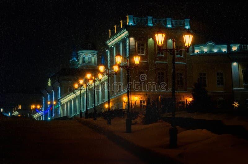 Улица ночи зимы в европейском городе Свет фонарика вдоль дороги с желтым светом, и в расстоянии стоковые изображения rf