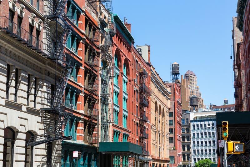 Улица с кирпичными зданиями и небоскребом стоковые изображения