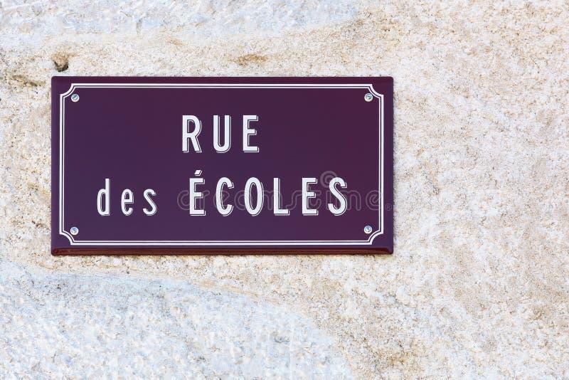 Улица школ подписывает на стене в французском стоковые изображения