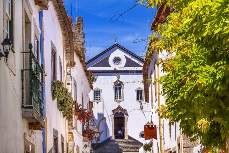 Улица Obidos Португалия узкой части церков Педра Sao белая стоковое фото