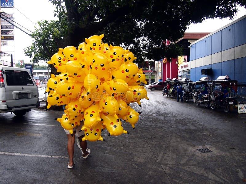 Уличный торговец продает воздушные шары сформированные pokemon стоковые фото