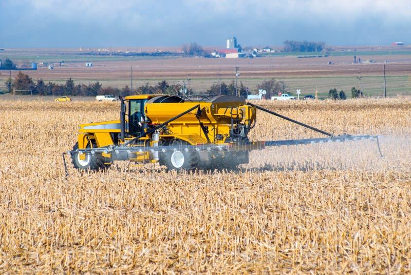 Удобрение фермера распыляя стоковое изображение