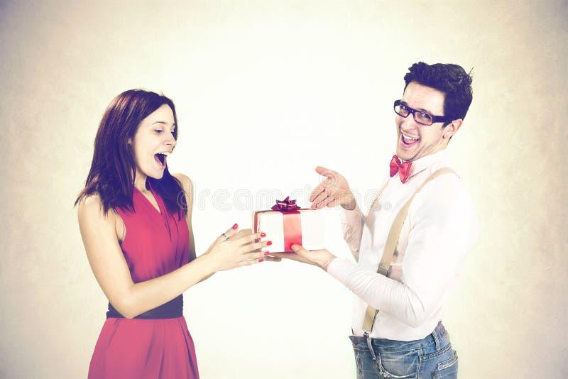 удовлетворенный парень давая специальный подарок к его подруге стоковое фото rf