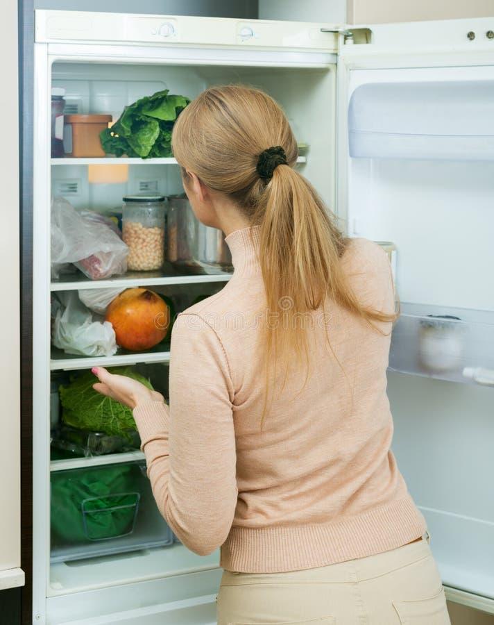 Удовлетворенный холодильник домохозяйки близко заполненный стоковая фотография