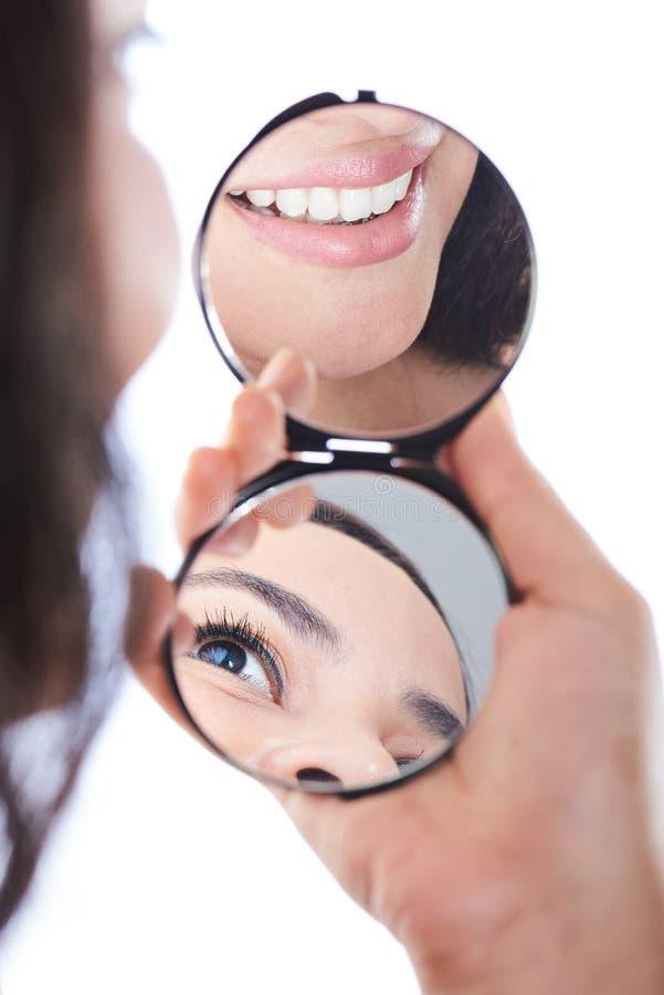 Улыбка девушки и зеркало отражения глаза в наличии стоковое изображение