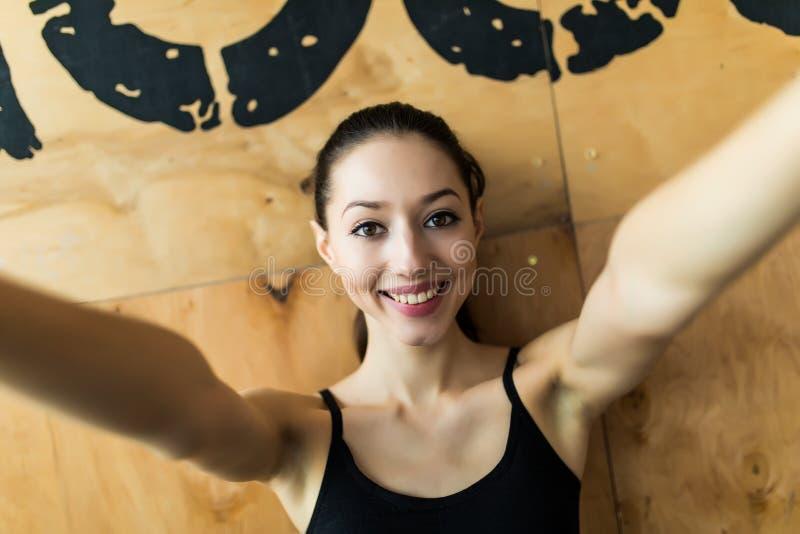 Улыбка женщины спорта на изображении собственной личности камеры на спортзале, изображении себя маленькой девочки работая фитнес- стоковое изображение rf