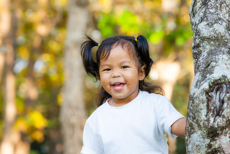 Улыбка маленькой девочки и смотреть камеру стоковое фото
