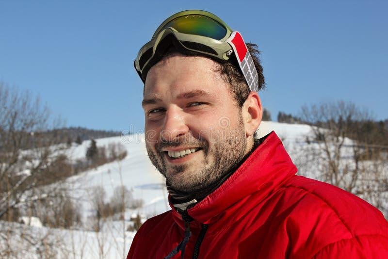 Улыбки молодого человека в зиме, сноуборде стоковое изображение rf