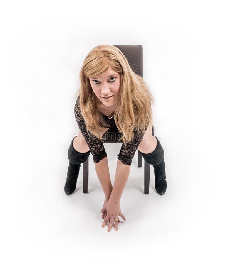 Улыбки молодой женщины на стуле стоковое изображение