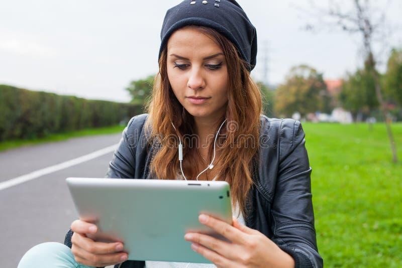 Ультрамодная женщина с наушниками ПК таблетки нося outdoors стоковое изображение rf