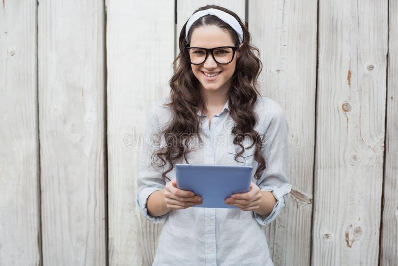 Ультрамодная молодая женщина с стильными стеклами используя ПК таблетки стоковые изображения rf