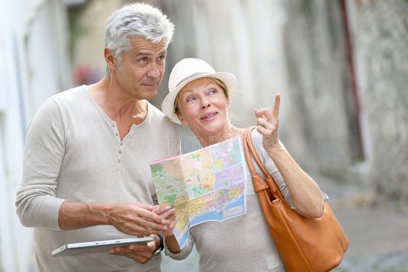 Ультрамодные старшие туристы посещая городок используя таблетку и карту стоковые фото