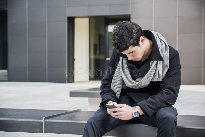 Ультрамодный красивый молодой человек в моде зимы используя усаживание сотового телефона стоковое изображение