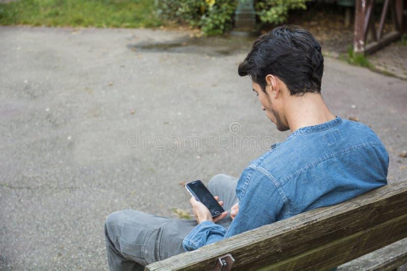 Ультрамодный красивый молодой человек используя сотовый телефон сидя на стенде стоковые фото