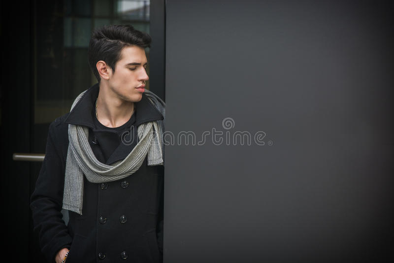 Ультрамодный красивый молодой человек стоя против стены в городской среде стоковые фотографии rf
