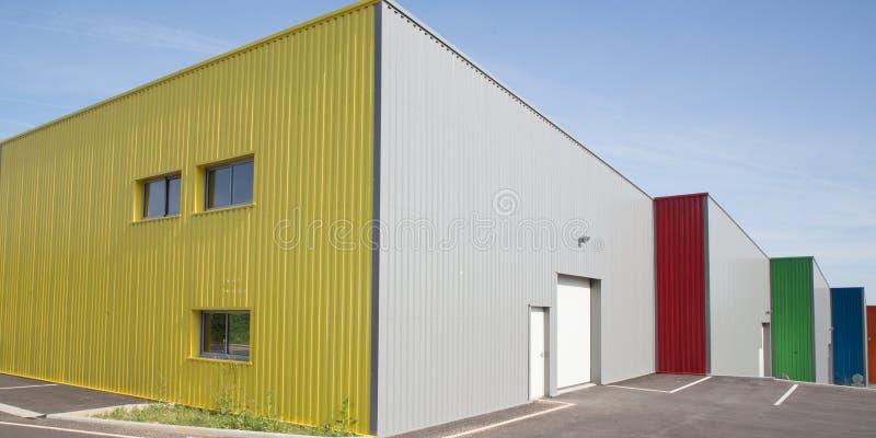 Фабрика строя серый фасад сделанный в алюминиевых панелях с дверями и окнах на промышленном месте стоковые фото