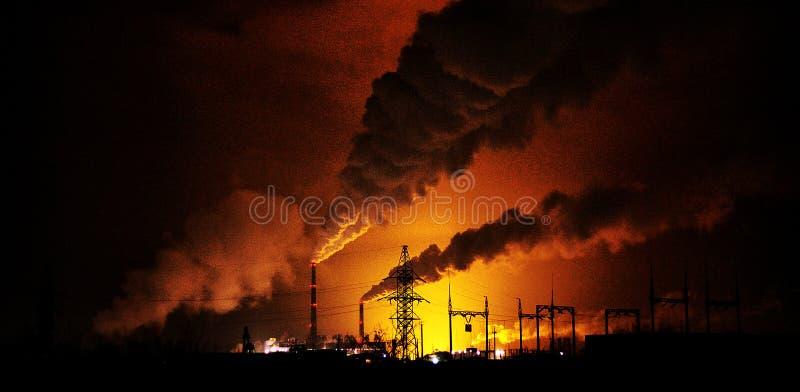 Фабрики на ноче, силуэты трубы производящ noxi стоковое изображение
