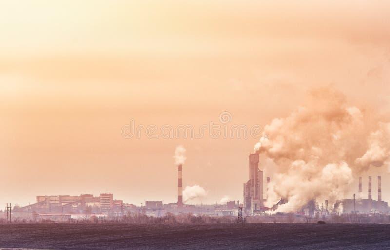 Фабрики с дымом от промышленной зоны труб пакостной загрязнянной в желтых и оранжевых тонах стоковые фотографии rf