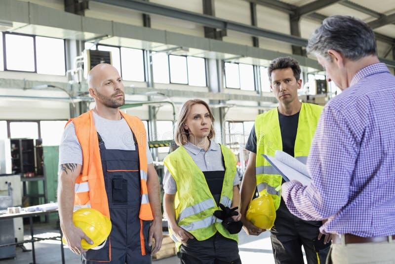 Файл мужского контролера рассматривая работниками физического труда в индустрии стоковые изображения