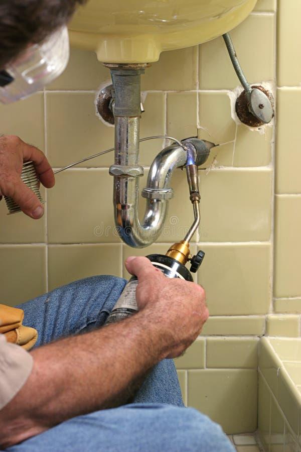 факел водопроводчика используя заварку стоковое фото
