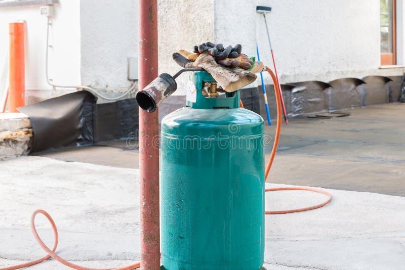Факел газового паяльника используемый для установки кренов войлока толя стоковое изображение rf