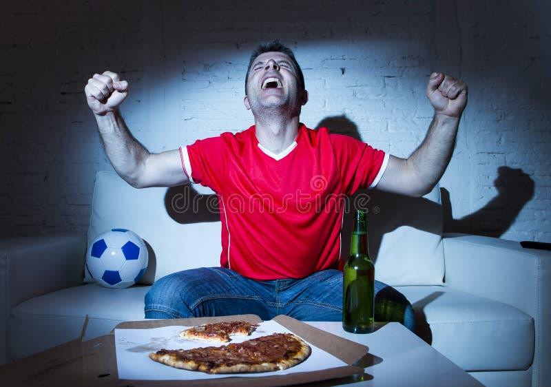 Фанатический человек футбольного болельщика смотря игру футбола на праздновать ТВ стоковое изображение rf