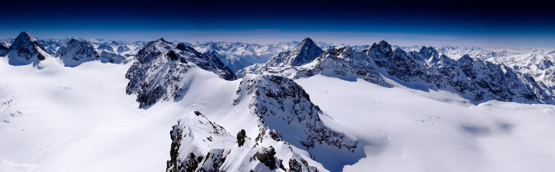 Фантастическая панорама горы зимы с целью высоких пиков и ледников гор Silvretta в швейцарских Альпах на быть стоковые изображения