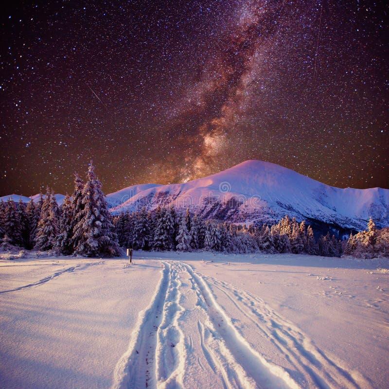 Фантастический метеорный поток зимы и снег-покрытые горы стоковые фотографии rf