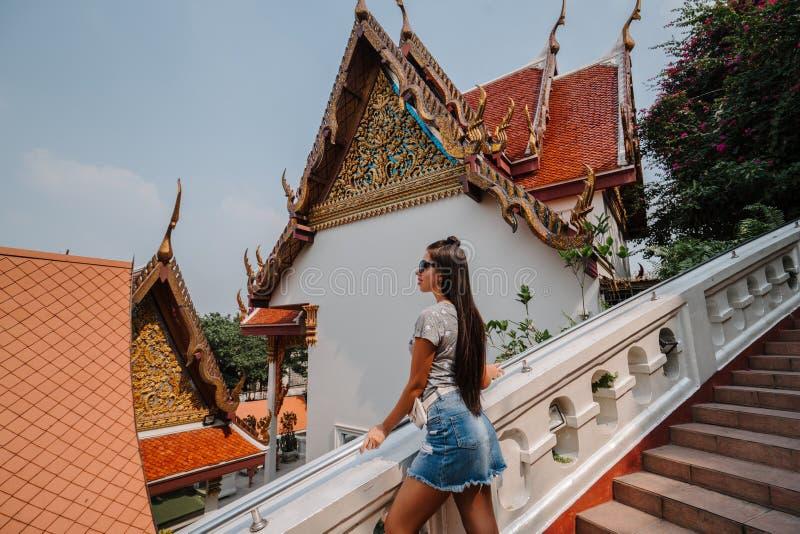 Фантастический, мистический, буддийский азиатский висок Женщина впечатленная с красотой места Туристская девушка идет через висок стоковая фотография