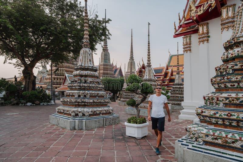 Фантастический, мистический, буддийский азиатский висок Турист на каникулах Человек идет вокруг старых пагод Wat Pho внутри стоковое фото rf
