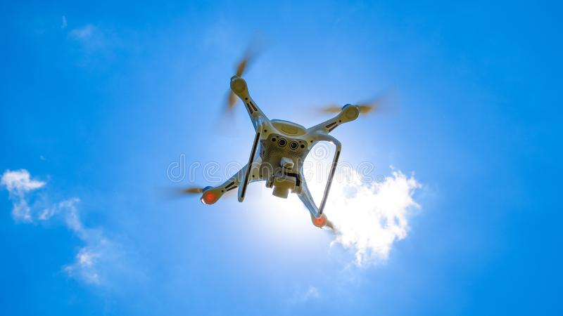 Фантом 4 трутня DJI в полете Quadrocopter против голубого неба стоковое изображение