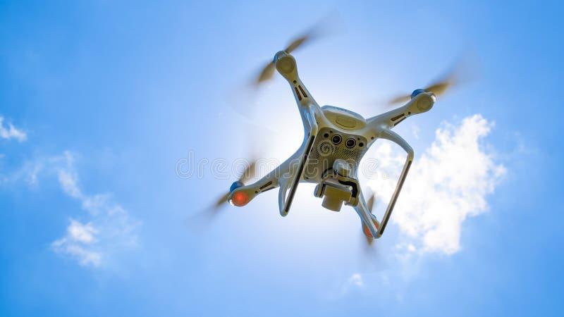 Фантом 4 трутня DJI в полете Quadrocopter против голубого неба стоковая фотография rf