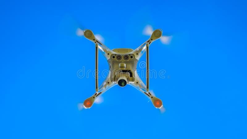 Фантом 4 трутня DJI в полете Quadrocopter против голубого неба стоковые изображения rf