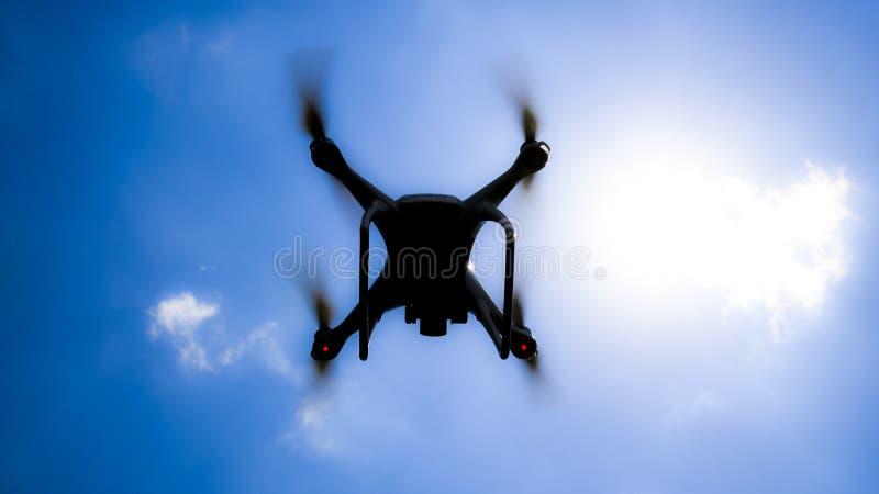 Фантом 4 трутня DJI в полете Quadrocopter против голубого неба с белыми облаками Полет вертолета в небе стоковое изображение