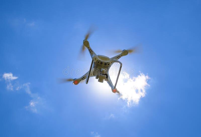 Фантом 4 трутня DJI в полете Quadrocopter против голубого неба стоковая фотография
