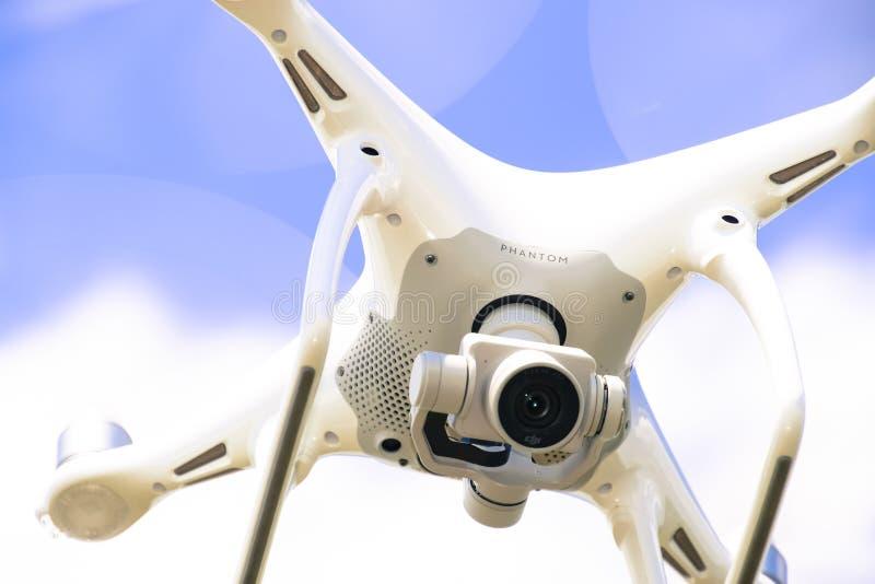 Фантом 4 трутня DJI в полете Quadrocopter против голубого неба стоковые фото