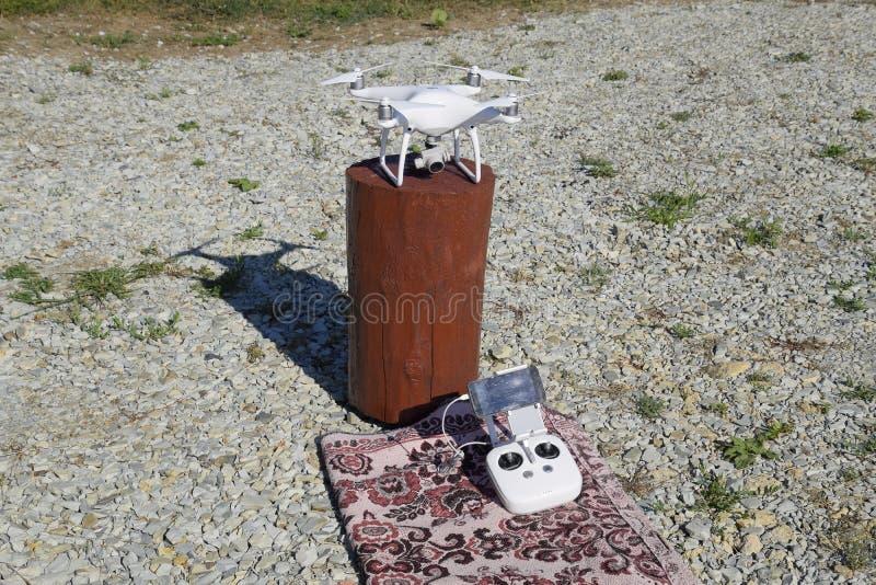 Фантом 4 Quadrocopter DJI на деревянной пеньке Подготавливать трутня для полета Dron новаторский робот летания стоковые фотографии rf