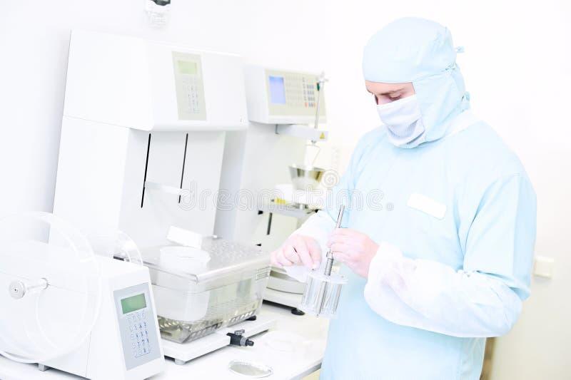 Фармацевтический исследователь с сыпучестью и тестер ссадины в лаборатории стоковые изображения