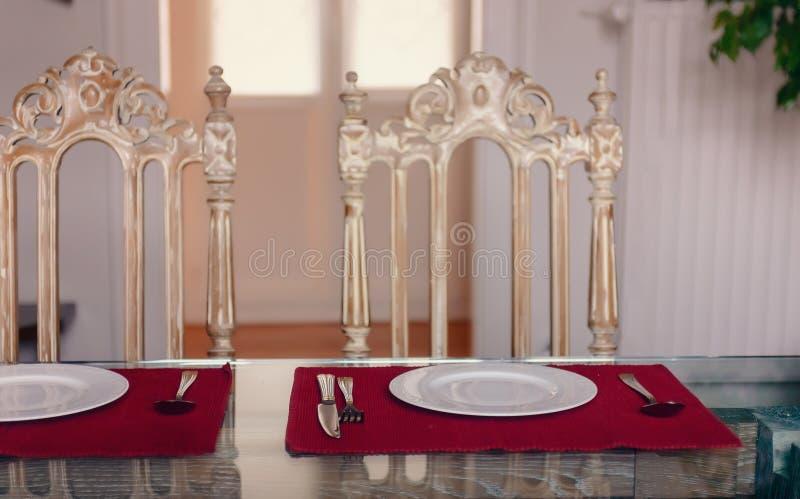 Фарфор кухонного стола покрывает вилку, нож, и стул 2 годов сбора винограда против окна стоковые изображения