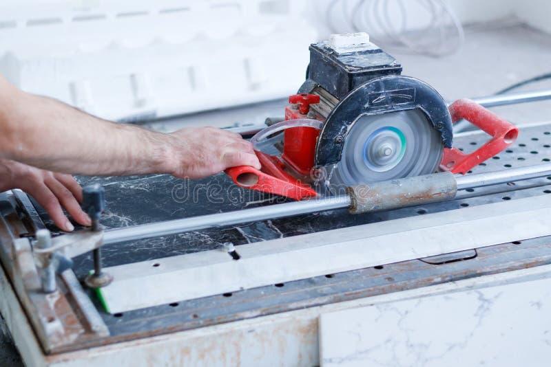 Фарфор рабочий-строителя tiler человека электрический режет плитку плиток стоковая фотография