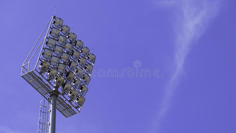 Фары возвышаются с поляком металла для арены спорт Установленный вокруг футбольного стадиона Предпосылка голубого неба стоковое фото