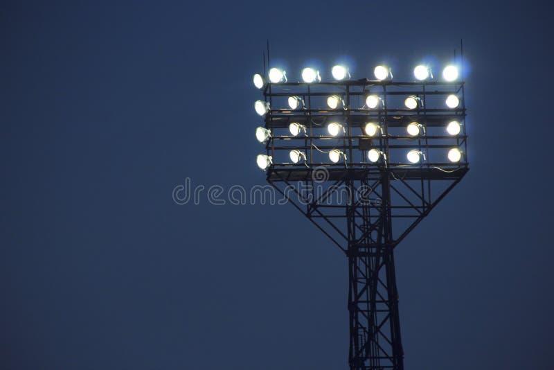 Фары освещают спичку промежутка времени футбольного поля Оборудование освещения для стадиона стоковая фотография
