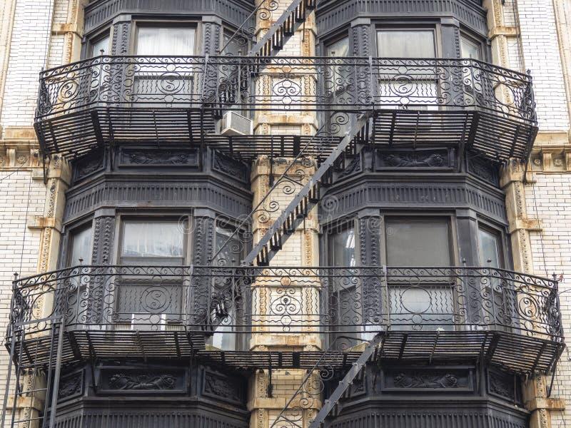 Фасады исторических зданий в районе Soho Нью-Йорка Характерные лестницы безопасности утюга на фасадах стоковые изображения rf