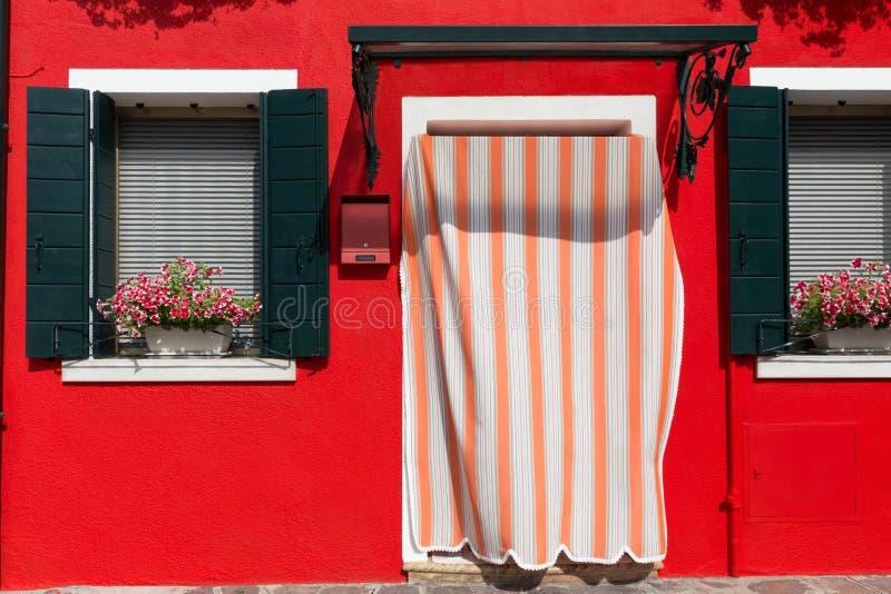 Фасад красно-покрашенного дома с красивым Среднеземноморск-стилем закрывает стоковое изображение