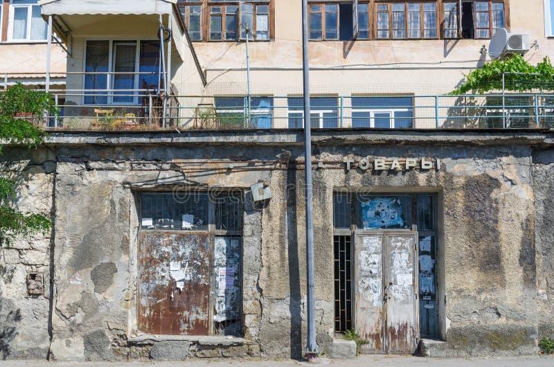 Фасад покинутого магазина с утилями объявлений на закрытых окнах и дверях стоковое фото
