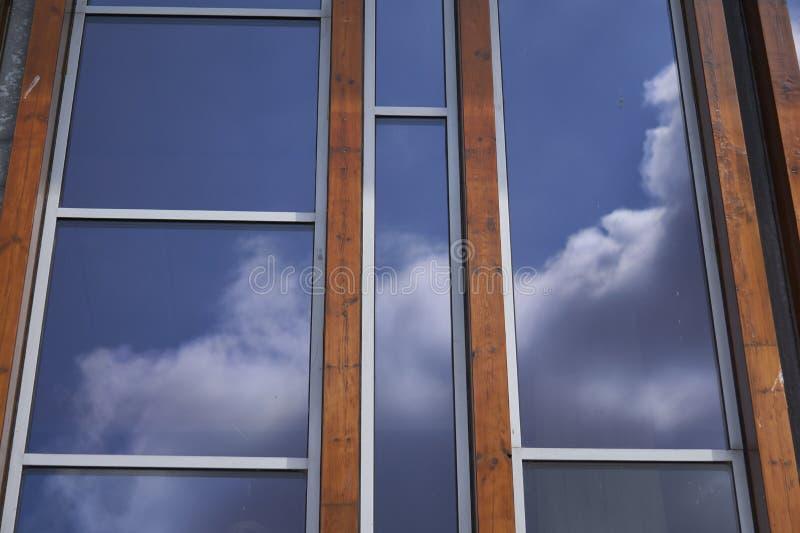 Фасад со стеклянной и тропической твердой древесиной отражая живое голубое небо с облаками стоковые изображения