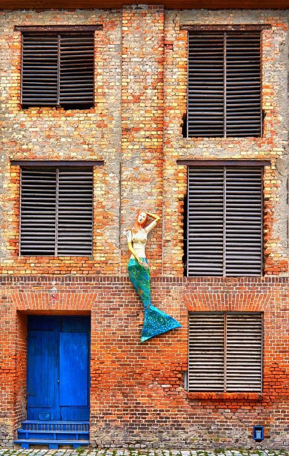 Фасад старого промышленного кирпичного дома с русалкой, старой дверью и окнами Старый город Стральсунд в Германии стоковое изображение rf