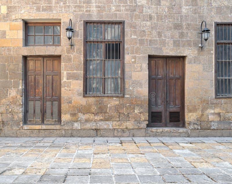 Фасад старой покинутой каменной стены кирпичей с деревянными дверями, окнами предусматриванными с стальными прутами и фонариками стоковые изображения